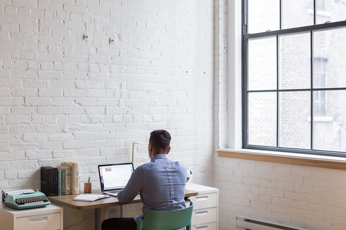 A man sits at his laptop in a home office